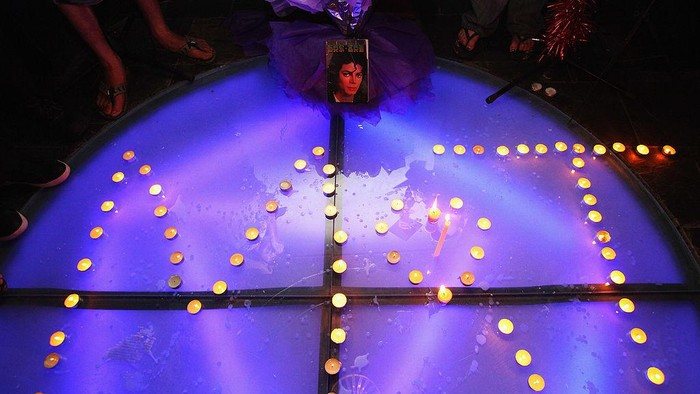 BEIJING - JUNE 26:  Chinese fans of Michael Jackson piece out the letter MJ with the candles as they gathered at a bar to commemorate him on June 26, 2009 in Beijing, China. Jackson, 50, the iconic pop star, died after going into cardiac arrest in a hospital on June 25 in Los Angeles, California.  (Photo by Feng Li/Getty Images)