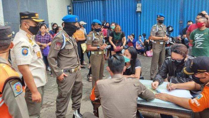 Situasi pendataan usai penggerebekan Diskotek Top One, Daan Mogot 1, Jakarta Barat, Jumat (3/7) pagi, yang terindikasi beroperasi di tengah masa Pembatasan Sosial Berskala Besar (PSBB) transisi fase 1 pandemi COVID-19. (Antara/Ricky Prayoga)