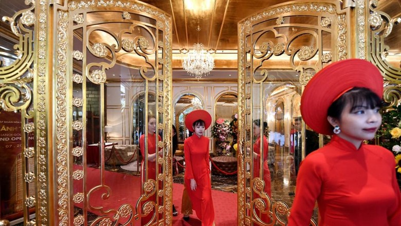 Staff wait to welcome guests in the lobby of the newly-inaugurated Dolce Hanoi Golden Lake hotel, the worlds first gold-plated hotel, in Hanoi on July 2, 2020. (Photo by Manan VATSYAYANA / AFP)