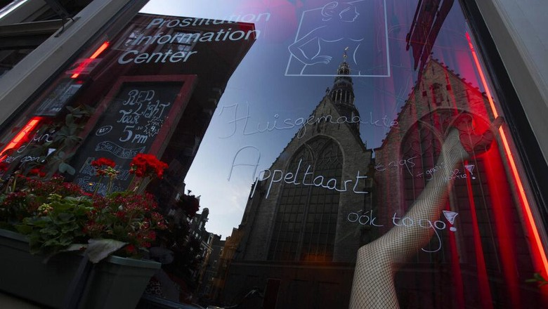 Oude Kerk, or Old Church, is reflected in the window of the PIC, Prostitution Information Center, as sex workers welcomed clients again in the Red Light District in Amsterdam, Netherlands, Wednesday, July 1, 2020. It wasnt quite business as usual as the capitals Red Light District emerged from coronavirus lockdown, but it was as close as it has been since the pandemic slammed the brakes on the worlds oldest profession. (AP Photo/Peter Dejong)