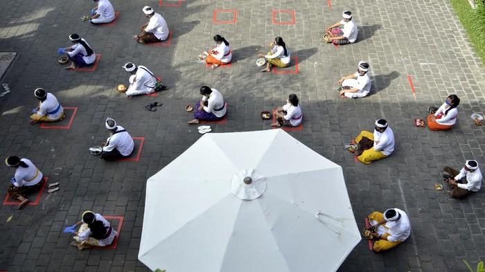 Umat Hindu mengenakan alat pelindung diri saat mengikuti rangkaian persembahyangan perayaan Hari Saraswati di Badung, Bali, Sabtu (4/7/2020). Perayaan Hari Raya Saraswati yang diperingati umat Hindu sebagai hari turunnya ilmu pengetahuan yang diselenggarakan di sebuah sekolah tersebut dilakukan dengan menerapkan protokol kesehatan secara ketat dan hanya diikuti oleh perwakilan guru, pegawai dan siswa dengan jumlah 25 orang sebagai upaya pencegahan COVID-19. ANTARA FOTO/Fikri Yusuf/hp.
