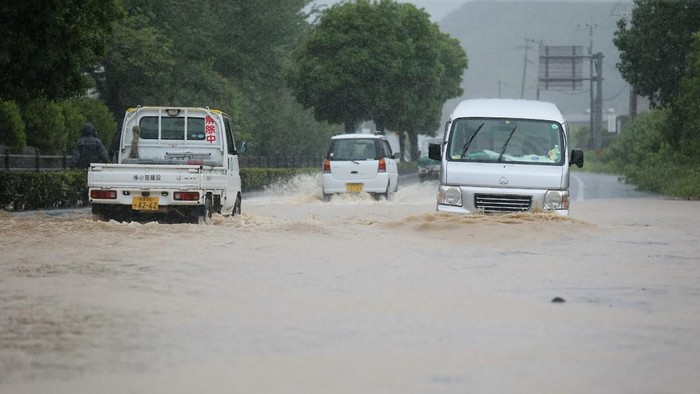 Vehicles pass through a flooded road caused by heavy rain in Yatsushiro, Kumamoto prefecture on July 4, 2020. - Some 75,000 people were ordered to evacuate in western Japan on July 4 as record heavy rain triggered floods and landslides, local media and officials said. The nations weather agency issued the highest level of heavy rain warnings to Kumamoto and Kagoshima on Kyushu island. (Photo by STR / JIJI PRESS / AFP) / Japan OUT