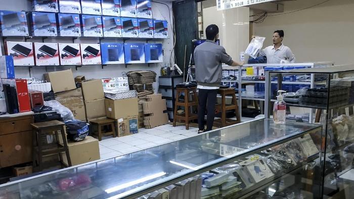 Pengendara ojek daring berada di depan pintu gerbang  Pasar Glodok, Jakarta, Sabtu (4/7/2020). Meski pihak pengelola menutup sementara Pasar Glodok selama tiga hari pada 2-4 Juli 2020 guna mencegah penyebaran COVID-19, masih banyak sejumlah toko yang buka dan melayani pembelian secara langsung.  ANTARA FOTO/Muhammad Adimaja/hp.