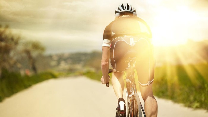 A racing bike rides alone on the roade - the sun rises / sunset