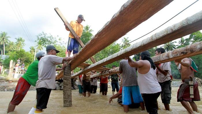 Warga di Desa Tulabolo, Gorontalo, bergotong royong membangun jembatan darurat. Jembatan sebelumnya diketahui rusak usai diterjang banjir beberapa waktu lalu.