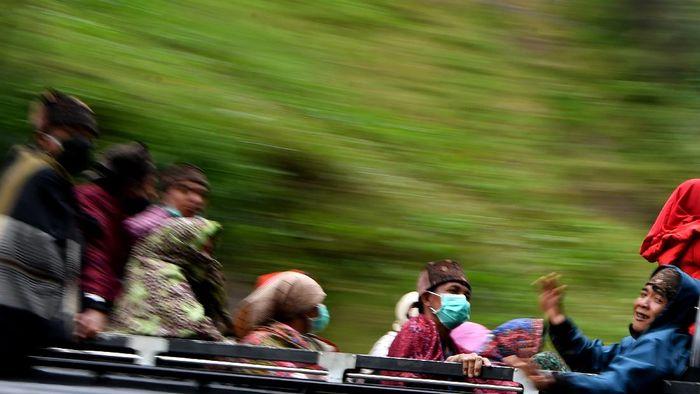 Masyarakat Suku Tengger dengan mengenakan masker berada di mobil bak terbuka menuju kawasan Gunung Bromo untuk melaksanakan perayaan Yadnya Kasada, Probolinggo, Jawa Timur, Senin (6/7/2020). Perayaan Yadnya Kasada merupakan bentuk ungkapan syukur masyarakat Suku Tengger dengan melarung sesaji berupa hasil bumi dan ternak ke kawah Gunung Bromo. ANTARA FOTO/Zabur Karuru/hp.