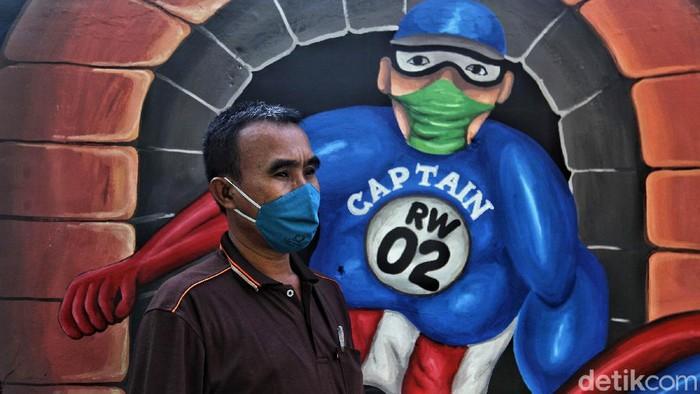 Warga melintas di depan mural bertemakan Lawan COVID-19 di kawasan Rawa Badak Selatan, Jakarta Utara, Senin (6/7). Menurut keterangan warga mural tersebut merupakan aksi lomba membuat mural bertemakan COVID-19 dengan tujuan mengkampanyekan untuk selalu menerapkan protkoler kesehatan di era New Normal.