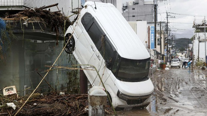 This aerial photo shows an overturned car at paddy field following a heavy rain in Hitoyoshi, Kumamoto prefecture, southern Japan  Sunday, July 5, 2020. Deep floodwaters and the risk of more mudslides hampered search and rescue operations on Sunday in southern Japan, including at elderly home facilities where more than a dozen perished and scores are still stranded. (Kyodo News via AP)