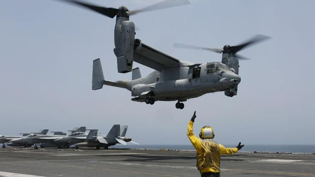 In this Friday, May 17, 2019, photo released by the U.S. Navy, Aviation Boatswain's Mate 2nd Class Nicholas Hawkins, from Houston, Texas, signals an MV-22 Osprey to land on the flight deck of the Nimitz-class aircraft carrier USS Abraham Lincoln in the Arabian Sea. Commercial airliners flying over the Persian Gulf risk being targeted by
