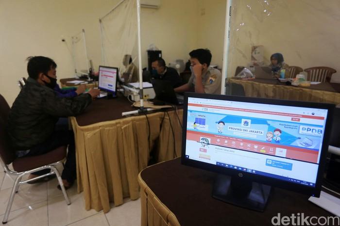 Orang tua murid melakukan pengaduan di Posko PPDB SMKN 27, Jakarta Pusat, Selasa (7/7/2020). Hari ini adalah tahap akhir dari Penerimaan Peserta Didik Baru (PPDB) DKI Jakarta 2020. Tahap akhir ini dibuka untuk mengisi kuota yang masih belum terisi oleh jalur zonasi hingga prestasi.