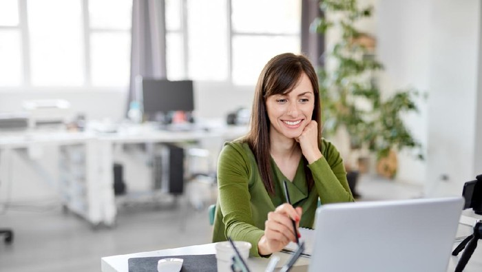Young Caucasian busy brunette smiling and holding pencil while sitting in office and looking at laptop.