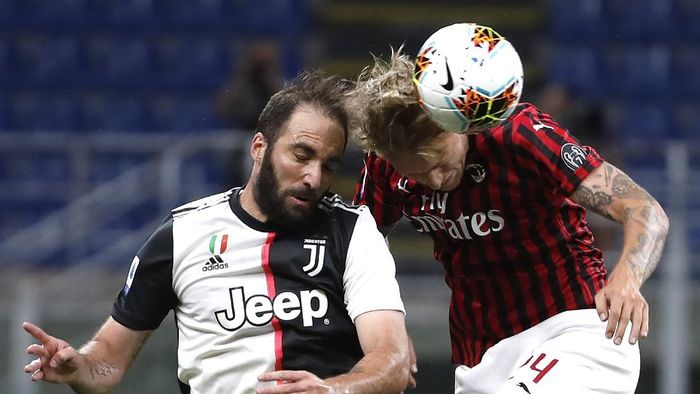 AC Milans Simon Kjaer, right, jumps for the ball with Juventus Gonzalo Higuain during the Serie A soccer match between AC Milan and Juventus at the San Siro stadium, in Milan, Italy, Tuesday, July 7, 2020. (AP Photo/Antonio Calanni)