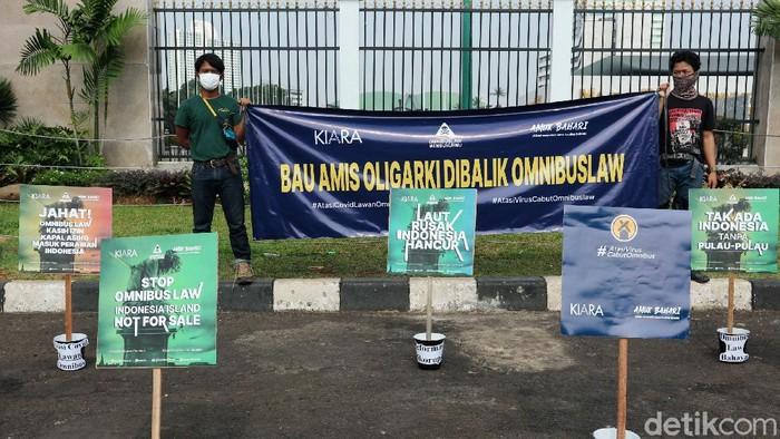 Aktivis Koalisi Rakyat untuk Keadilan Perikanan (KIARA) melakukan aksi dengan membawa ikan di depan Gedung DPR, Jakarta, Rabu (8/7/2020). Dalam aksinya mereka menolak Rancangan Undang-Undang Omnibus Law Cipta Kerja. Mereka berpendapat RUU ini disusun dan dibahas bukun untuk melindungi masyarakat dan sumber daya alam Indonesia melainkan sebaliknya untuk memanjakan kepentingan oligarki yang telah lama menguasai kebijakan di negara ini.