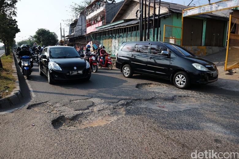 Pengendaran melewati jalan rusak di Jalan I Gusti Ngurah Rai, Bintara, Kota Bekasi, Jawa Barat, Rabu (8/7/2020). Jalan penghubung kota Bekasi dan Jakarta di beberapa titik mengalami kerusakan. Salah satunya di Jalan I Gusti Ngurah Rai, tepatnya di RT 006 RW 014, Kelurahan Bintara, Bekasi Barat, Jawa Barat. Jalan disini berlubang cukup dalam yang mengharuskan pengendara berhati-hati. Kerusakan ini disebabkan buruknya drainase dikawasan tersebut. Kerusakan sudah terjadi sejak bulan Januari hingga kini tidak ada perbaikan.