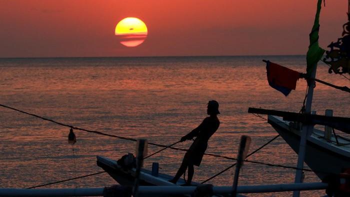 Kapal melintas saat matahari terbenam di dermaga Penarukan, Situbondo, Jawa Timur, Selasa (7/7/2020). Dermaga Penarukan yang difungsikan untuk bongkar muat hasil tangkapan nelayan dan angkutan barang ke kepulauan madura itu, juga ramai dikunjungi warga untuk melihat matahari terbenam. ANTARA FOTO/Budi Candra Setya/hp.