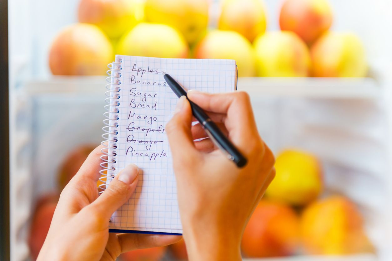Close-up of woman checking shopping list with apples in the background