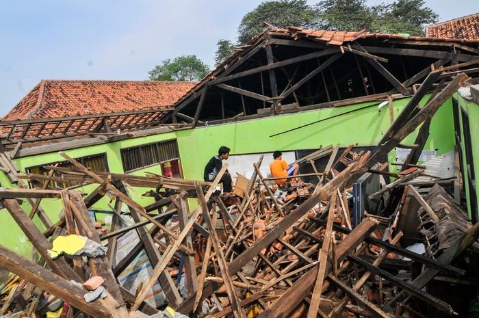 Sejumlah warga mengamati atap Sekolah Dasar Negeri (SDN) 03 Sindangsari yang ambruk di Cabangbungin, Kabupaten Bekasi, Jawa Barat, Kamis (9/7/2020). Menurut pihak sekolah atap 2 ruang kelas ambruk pada (23/6/2020) akibat kondisi bangunan yang sudah lama dan tidak ada korban jiwa pada kejadian tersebut. ANTARA FOTO/ Fakhri Hermansyah/nz