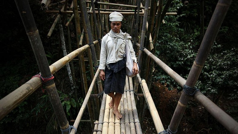 BANTEN, INDONESIA - FEBRUARY 07:  A member of the traditional Baduy (or Badui) tribe walks on the bamboo bridge in the village in the hilly forest area of the Kendeng mountains on February 7, 2010 in Banten, Indonesia. The traditional community consists of around 5000-8000 people spread acorss a hilly area of just 50 square kilometres. The religion of the Baduy people, known as Agama Sunda Wiwitan, combines elements of Hinduism, Buddhism and traditional beliefs, including various taboos such as not eating food at night, touching money, accepting gold or silver or even cutting their hair.  (Photo by Ulet Ifansasti/Getty Images)