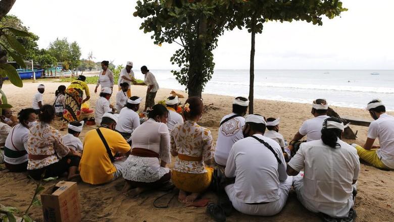 Orang-orang menyaksikan matahari terbit di sebuah pantai di Bali, Indonesia, Kamis (9/7/2020). Pulau resort di Bali dibuka kembali setelah tiga bulan terkunci akibat pandemi virus Corona pada Kamis ini. Pembukaan tahap pertama ini hanya untuk wisatawan dan penduduk lokal serta sebagian turis asing yang terdampar untuk melanjutkan kegiatan publik sebelum kembali dibuka untuk kedatangan orang asing pada September mendatang. (Foto AP / Firdia Lisnawati)