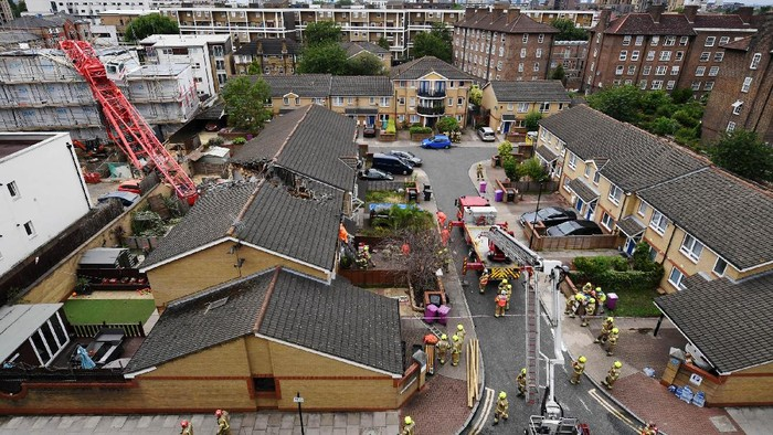 BOW, ENGLAND - JULY 08: Emergency services work at the scene where a 20-metre crane has collapsed onto a terraced house in East London on July 8, 2020 in Bow, England. The London Fire Brigade are working to rescue people trapped in a terraced house after a 20-meter crane on a nearby building site has collapsed. (Photo by Chris J Ratcliffe/Getty Images)