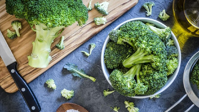 Top view of a bowl full of broccoli branches surrounded by a wooden cutting board with a entire broccoli and a kitchen knife on top, an olive oil bottle, a metal colander and a little wooden tray with salt on a grey textured backdrop. Low key DSLR photo taken with Canon EOS 6D Mark II and Canon EF 24-105 mm f/4L