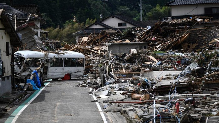 Debris litter a village following heavy rains and flooding in the village of Kuma, Kumamoto prefecture on July 8, 2020. - Japan will deploy more troops to search for survivors of devastating floods and landslides that have killed at least 52 people in the southwest of the country, Prime Minister Shinzo Abe pledged (Photo by CHARLY TRIBALLEAU / AFP) / The erroneous mention[s] appearing in the metadata of this photo by CHARLY TRIBALLEAU has been modified in AFP systems in the following manner: [Kumamura] instead of [Kuma mura]. Please immediately remove the erroneous mention[s] from all your online services and delete it (them) from your servers. If you have been authorized by AFP to distribute it (them) to third parties, please ensure that the same actions are carried out by them. Failure to promptly comply with these instructions will entail liability on your part for any continued or post notification usage. Therefore we thank you very much for all your attention and prompt action. We are sorry for the inconvenience this notification may cause and remain at your disposal for any further information you may require.