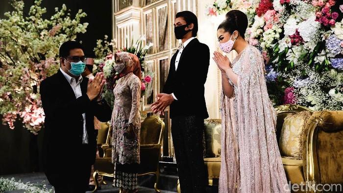 Prosesi pernikahan mengalami sejumlah modifikasi dalam penerapannya di era new normal. Di antaranya dengan menerapkan protokol kesehatan. Penasaran? Yuk, lihat.