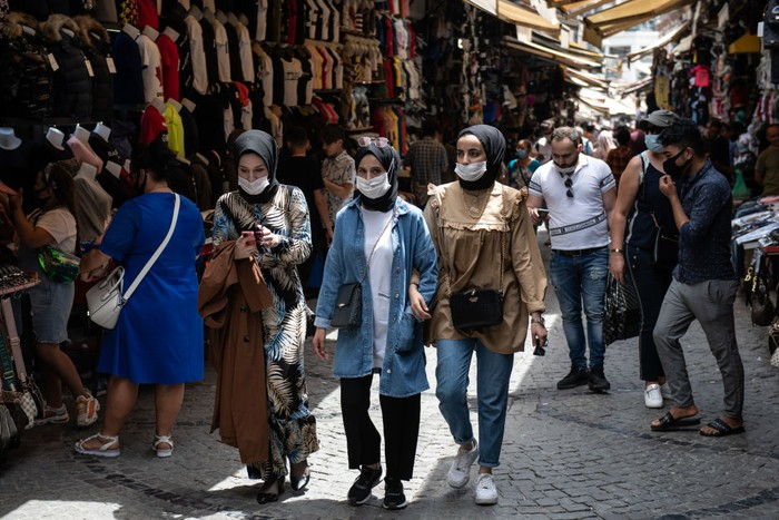 ISTANBUL, TURKEY - JULY 09: People wearing face masks shop in a market street in Eminonu on July 09, 2020 in Istanbul, Turkey. Turkey continues to ease restrictions after recently reopening, cafes, restaurants, parks, inter-city travel and selected businesses, giving retailers, shopping malls and tourist operators hope that the economy will be reactivated. After easing restrictions, Turkey's consumer confidence index edged up to 62.6 points in June from 59.5 the previous month. As of July 09, Turkey has reported 5,300 coronavirus-related deaths and 209,962 confirmed cases. (Photo by Burak Kara/Getty Images)