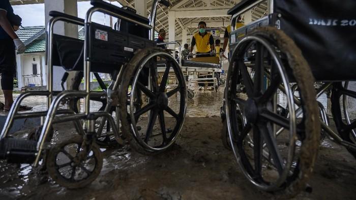 Petugas mengamankan barang-barang di dalam ruang perawatan yang digenangi lumpur di Rumah Sakit Umum Daerah (RSUD) Torabelo, Kabupaten Sigi, Sulawesi Tengah, Jumat (10/7/2020). Genangan lumpur yang disebabkan oleh luapan sungai di belakang rumah sakit tersebut terjadi pada Kamis (9/7/2020) petang akibat hujan deras dan mengakibatkan sebagian besar pasien meninggalkan rumah sakit kecuali yang diisolasi karena COVID-19. ANTARAFOTO/Basri Marzuki/pras.