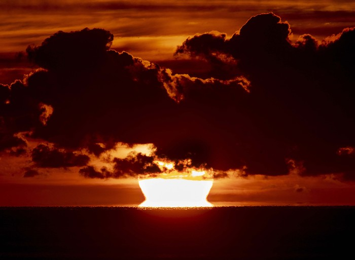 The rising sun is seen between clouds over the pier of Scharbeutz at the Baltic Sea, Germany, Monday, July 6, 2020. (AP Photo/Michael Probst)