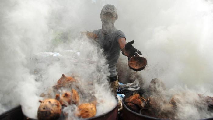 Pekerja mengemas arang batok ke dalam karung di Kuala Jambi, Tanjungjabung Timur, Jambi, Jumat (10/7/2020). Tempat produksi yang berada di sentra komoditas kelapa Provinsi Jambi tersebut mampu menghasilkan 500 kilogram arang batok per hari yang dipasarkan ke sejumlah daerah di pulau Sumatera dan Jawa. ANTARA FOTO/Wahdi Septiawan/pras.
