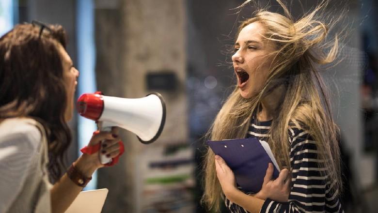 Rude female leader yelling at her coworker through megaphone.