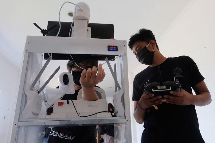 Mahasiswa memeriksa tekanan darah dengan menggunakan robot rakitan saat melakukan uji coba di ruang Unit Kegiatan Mahasiswa (UKM) Robotec Universitas Udayana, Denpasar, Bali, Jumat (10/7/2020). Robot hasil karya mahasiswa Teknik Elektro dan Teknik Mesin tersebut dilengkapi alat untuk memeriksa tekanan darah, suhu tubuh dan tempat pengiriman makanan maupun obat-obatan bagi pasien sehingga ditargetkan dapat membantu tugas tenaga medis yang berisiko tinggi dalam menangani penderita COVID-19. ANTARA FOTO/Nyoman Hendra Wibowo/nym/wsj.