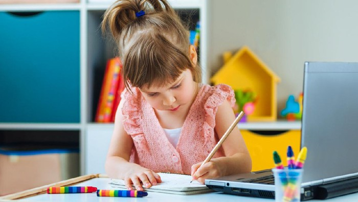 Beautiful little girl writing homework using notebook for distance learning in the kids room. Distance online learning concept.