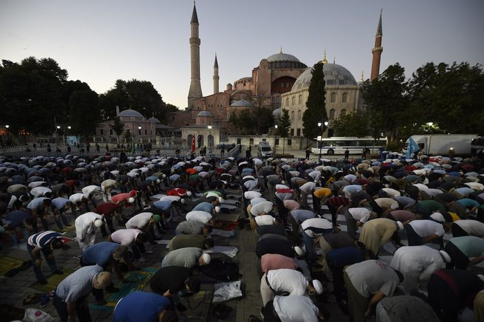 Muslims offer their evening prayers outside the Byzantine-era Hagia Sophia, one of Istanbuls main tourist attractions in the historic Sultanahmet district of Istanbul, following Turkeys Council of States decision, Friday, July 10, 2020. Turkeys highest administrative court issued a ruling Friday that paves the way for the government to convert Hagia Sophia - a former cathedral-turned-mosque that now serves as a museum - back into a Muslim house of worship. The Council of State threw its weight behind a petition brought by a religious group and annulled a 1934 cabinet decision that changed the 6th century building into a museum.