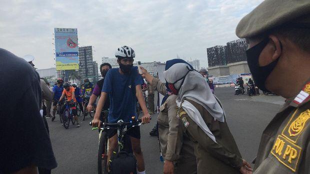 Suhu tubuh warga diperiksa sebelum diizinkan memasuki kawasan CFD di Jalan Jend Ahmad Yani, Kota Bekasi, MInggu (12/7/2020).