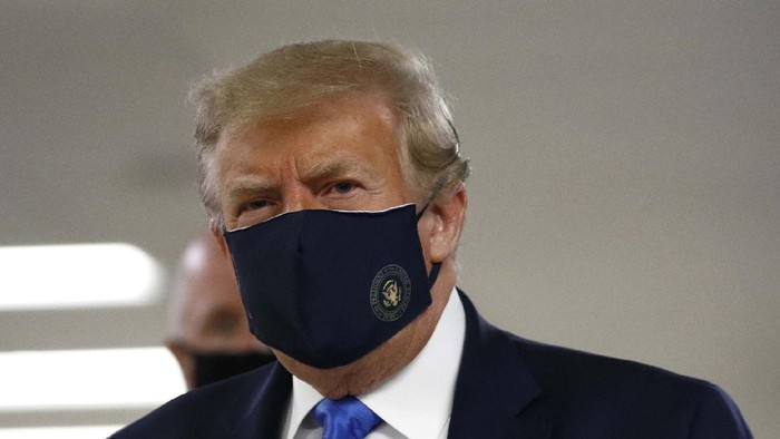 President Donald Trump, center, wearing a mask as he walks down the hallway during his visit to Walter Reed National Military Medical Center in Bethesda, Md., Saturday, July 11, 2020. (AP Photo/Patrick Semansky)