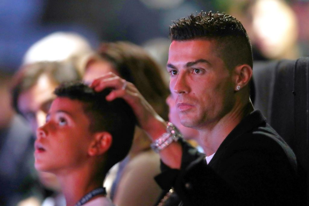 LONDON, ENGLAND - NOVEMBER 12:  Cristiano Ronaldo and son Cristiano Ronaldo Jr. watch on during the singles round robin match between Novak Djokovic of Serbia and John Isner of The United States during Day Two of the Nitto ATP Finals at The O2 Arena on November 12, 2018 in London, England.  (Photo by Naomi Baker/Getty Images)