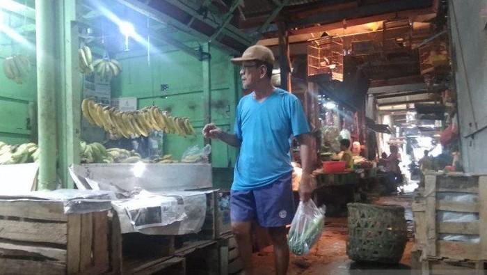 Pegunjung sedang menenteng kantong plastik berisi belanjaannya di Pasar Cempaka Putih, Jakarta Pusat, Jumat (28/02/2020). (ANTARA/Mochamad Firdaus)