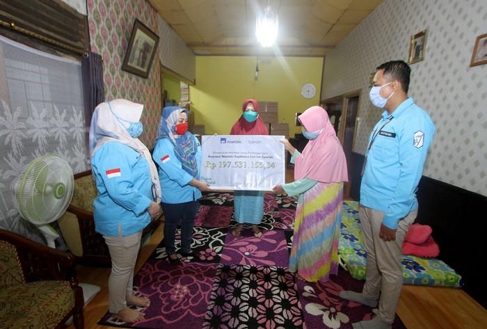 Perwakilan PT AXA Mandiri Financial Services (AXA Mandiri) Rini (dua kiri) menyerahkan pembayaran klaim asuransi jiwa secara simbolis kepada ahli waris nasabah AXA Mandiri Amaliah (dua kanan) di Banjarmasin, Kalimantan Selatan. Melalui manfaat perlindungan asuransi jiwa tersebut, keluarga yang ditinggalkan dapat terbantu secara finansial untuk terus melanjutkan hidup, ketika tulang punggung keluarga tutup usia. AXA Mandiri telah menyediakan perlindungan asuransi kepada lebih dari satu juta nasabah, serta telah membayarkan klaim dan maanfaat sebesar Rp 5,3 triliun pada tahun 2019 lalu. dok. AXA Mandiri