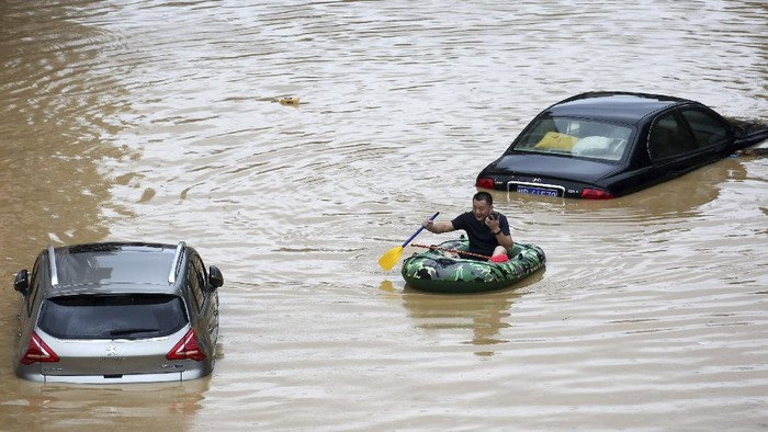 In this photo released by Xinhua News Agency, a man paddles with an inflatable boat past submerged cars during a flood in Rongshui County in southern Chinas Guangxi Zhuang Autonomous Region, Saturday, July 11, 2020. Vice Minister of Emergency Management Zheng Guoguang told reporters Monday, July 13, 2020 that the Yangtze River and parts of its watershed have seen the second highest rainfall since 1961 over the past six months. (Long Linzhi/Xinhua via AP)