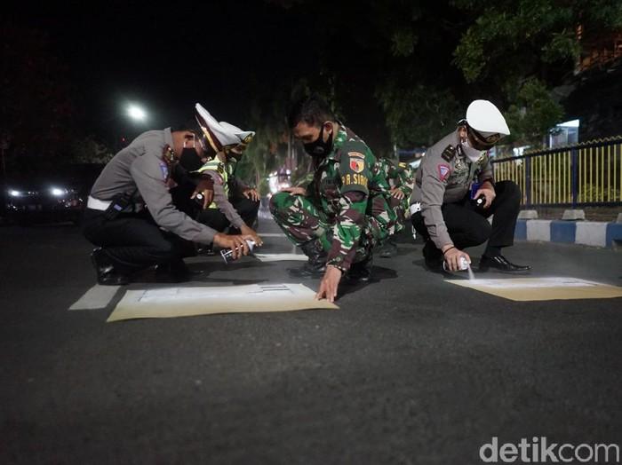 Aspal di sejumlah traffic light di Kota Probolinggo dicat. Nantinya, pengendara motor yang berhenti di traffic light bisa menerapkan physical distancing.