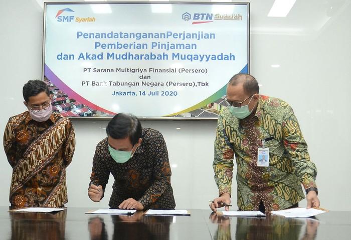 Direktur Utama PT Bank Tabungan Negara (Persero) Tbk, Pahala N. Mansury  bersama  Direktur Finance, Planning & Treasury Bank BTN Nixon L.P Napitupulu (kiri), Direktur Utama PT Sarana Multigriya Finansial (Persero)  Ananta Wiyogo (kedua kanan) dan Direktur SMF Heliantopo (kanan) menunjukkan Perjanjian Kerjasama (PKS) terkait pinjaman sebesar Rp 850 miliar di Jakarta, Selasa (14/7). Dana tersebut  akan disalurkan Bank BTN  dalam bentuk KPR Subsidi baik dengan skema Fasilitas Likuiditas Pembiayaan Perumahan atau FLPP maupun Subsidi Selisih Bunga (SSB) untuk mendukung Program Sejuta Rumah yang dicanangkan Pemerintah.