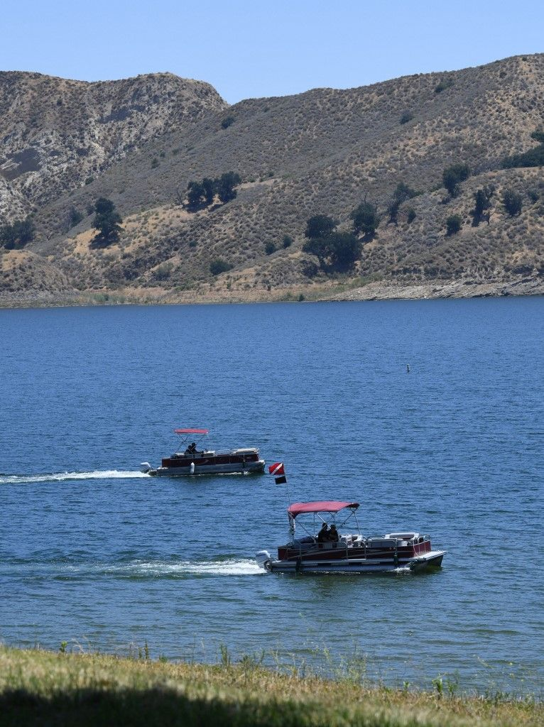Ventura County Sheriff's deputies stand near a vehicle near the shoreline at Lake Piru, north of Los Angeles, California, on July 13, 2020, where a body presumed to be missing