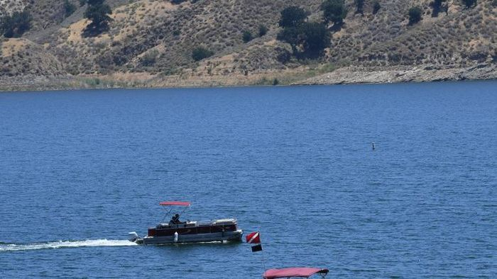 Ventura County Sheriffs deputies stand near a vehicle near the shoreline at Lake Piru, north of Los Angeles, California, on July 13, 2020, where a body presumed to be missing