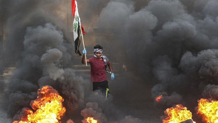 Protesters burn tires in front of the provincial council building during a demonstration demanding better public services and jobs and against corruption in Basra, southeast of Baghdad, Iraq, Tuesday, July 14, 2020. (AP Photo/Nabil al-Jurani)