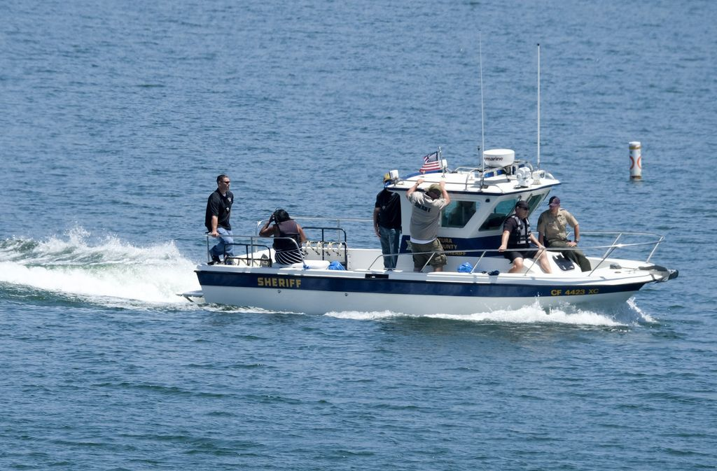 Naya Rivera's father, George Rivera, right, and mother Yolanda, left, with members of Ventura County Sheriff's Office are seen in a boat after Naya Rivera's body was found in Lake Piru, Monday, July 13, 2020, in Lake Piru, Calif. (AP Photo/Ringo H.W. Chiu)