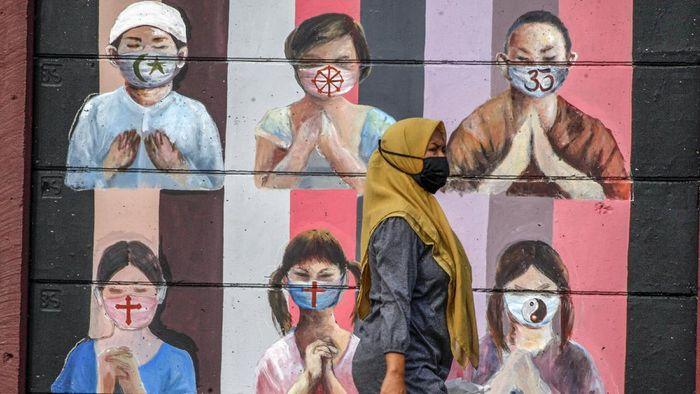 Warga melintas di dekat mural bergambar simbol orang berdoa menggunakan masker yang mewakili umat beragama di Indonesia di kawasan Juanda, Kota Depok, Jawa Barat, Kamis (18/6/2020). Mural yang dibuat oleh warga itu bertujuan untuk memberikan edukasi kepada masyarakat untuk menggunakan masker sebagai salah satu  pencegahan dan penyebaran COVID-19. ANTARA FOTO/Yulius Satria Wijaya/aww.