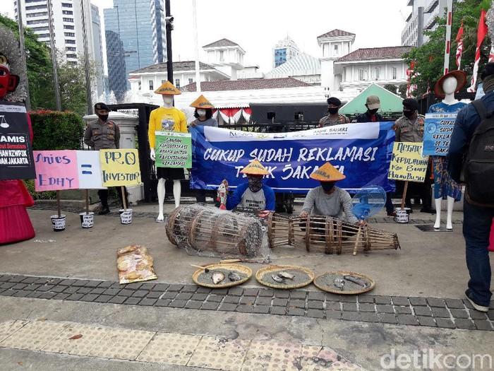 Massa KIARA membawa ikan busuk saat aksi menolak reklamasi Ancol di depan Balkot DKI.