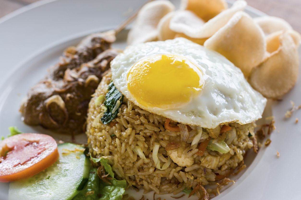 A popular fried rice dish in Indonesia and Malaysia. Served with egg, chicken satay, prawn crackers and salad garnish.